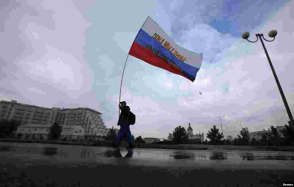 "A fan carries a Russian flag bearing the words ""When we are together we shall win"" near the Olympic Park in Sochi. (Reuters/Eric Gaillard)"