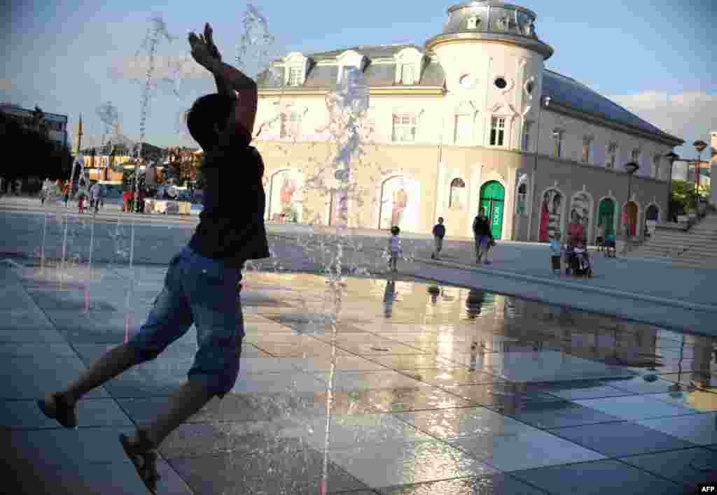 A boy cools off in a fountain during sunset in Pristina, Kosovo. (AFP/Armend Nimani)