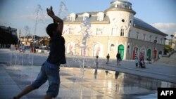 Një djalë duke luajtur me ujë të fontanave në sheshin e Prishtinës. (Foto nga arkivi)