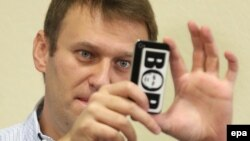 "Russian opposition leader Aleksei Navalny takes pictures with his mobile phone decorated with a sticker depicting Russia's President Vladimir Putin inside the middle letter of the Russian word 'BOP' (""thief"") in a courtroom in Kirov on October 16."