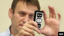 """Оппозиционер А.Навальный бүгүнкү сотто президент В.Путиндин сүрөтү """"ВОР"""" (Ууру) деген сөздүн ичинде жазылган чөнтөк телефонуна сүрөт тартып отурду, Киров, 16-октябрь, 2013."""