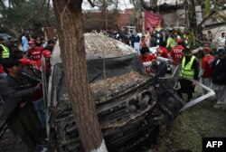 Volunteers and media representatives examine the wreckage of a vehicle after a suicide bomb attack in Peshawar on February 15.