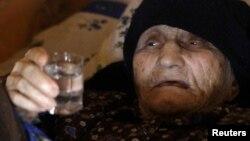 """Антиса Хвичаваның """"129 жасқа келдім"""" деген кезіндегі суреті. """"Чача"""" сусынын ұстап жатыр. Грузия, Сачино ауылы, 11 наурыз 2010 жыл."""