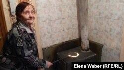 80-летняя жительница многоэтажного дома Галина Осипова сидит рядом с самодельной печкой-буржуйкой. Поселок Шахан, Карагандинская область, 10 января 2017 года.