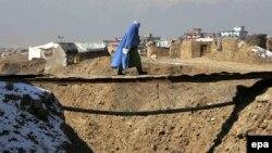 Кабулдың шетінде жыра үстіндегі көпірмен өтіп бара жатқан пәренжі киген әйел. 2 қаңтар 2014 жыл. (Көрнекі сурет.)