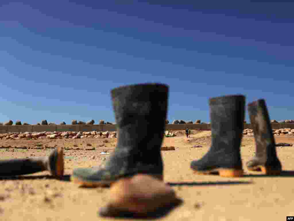 Boots abandoned by foreign workers next to a makeshift camp near the Libyan port of Benghazi on February 28. Photo by Patrick Baz for AFP