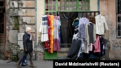 GEORGIA -- A woman walks past by a second hand shop in Tbilisi, February 16, 2018
