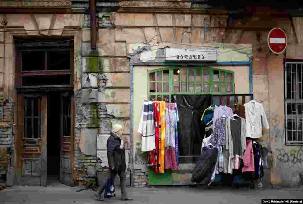 A woman walks by a second hand shop in Tbilisi, Georgia. (Reuters/David Mdzinarishvili)