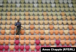 A worker cleans seats in the newly refurbished Sukhumi stadium, which has been revamped ahead of the soccer tournament.
