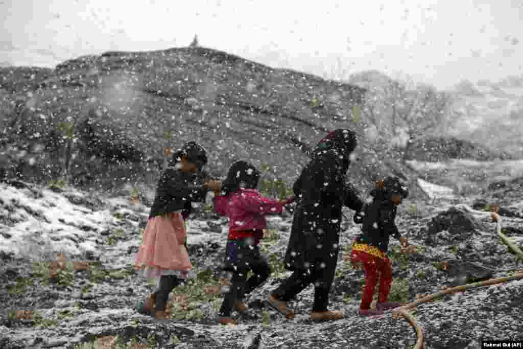 Afghan children walk during a snowfall on the outskirts of Kabul. (AP/Rahmat Gul)