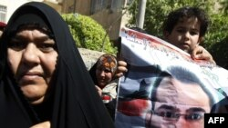 A young relative of Iraqi journalist Muntadhir al-Zaidi holds up his picture during his trial in March.