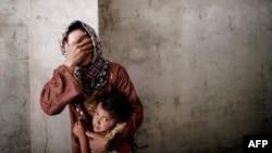 Жанчына з дачкой ў часе паветраных атакаў урадавых войскаў у перадмесьці Алепа. 13 верасьня 2012 г.
