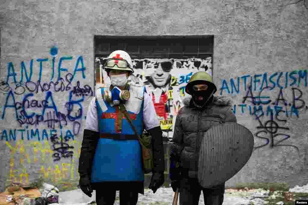 A medic of the antigovernment protest camp (left) poses for a portrait with his security guard at the barricades near the site of clashes with riot police in Kyiv on January 28. (Reuters/Thomas Peter)