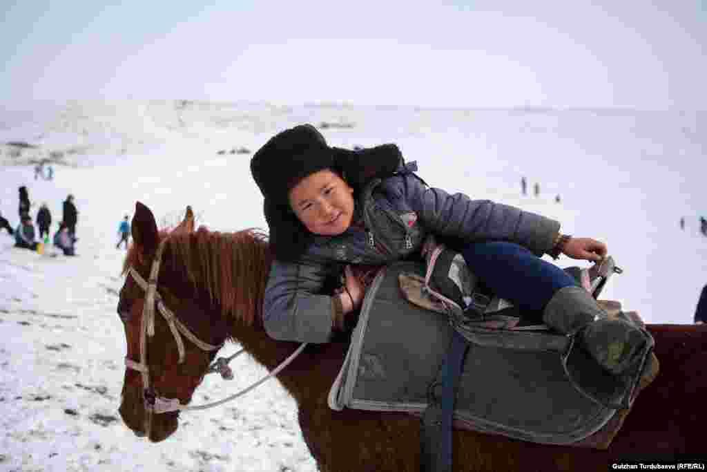 Мальчик взбирается на лошадь в Чуйской области в Кыргызстане. 23 февраля 2019 года. (Gulzhan Turdubaeva, RFE/RL)