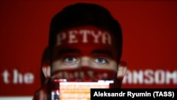 Проекция названия вируса Petya на лице анонимного молодого человека