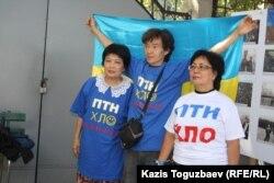 Гражданские активисты фотографируются на фоне флага Украины. Алматы, 30 августа 2014 года.