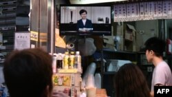 تعدادی از شهروندان هنگکنگ در یک کافه و در حال تماشای سخنان کری لام درباره توقف لایحه استرداد