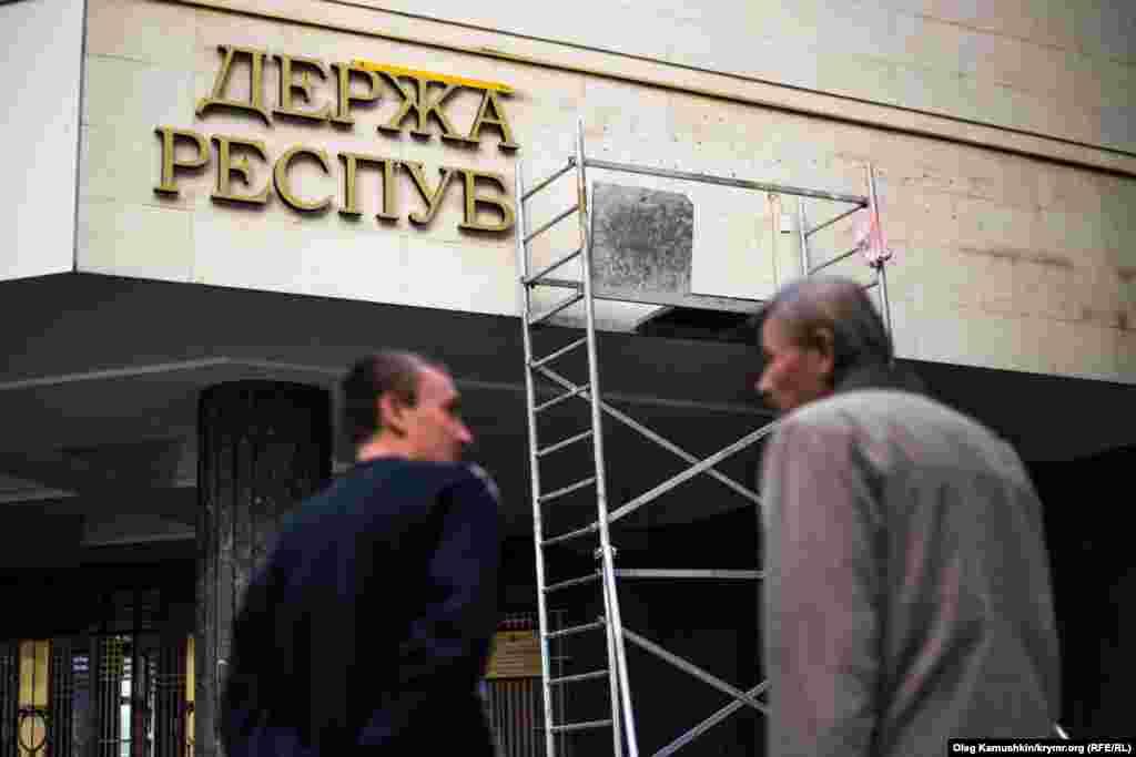 Кілька робітників, піднявшись на будівельні ліси, встановлюють на фасад будівлі українську назву самопроголошеного кримського парламенту: «Державна Рада Республiки Крим».