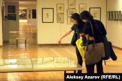 """Девушки у экспонатов выставки """"Парад шаржей"""" в Алматы."""