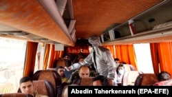 IRAN -- A member of Iranian red crescents test passengers of a bus for possible coronavirus Covid 19 symptoms, as police blocked Tehran to Alborz highway to check every car following ordered by Iranian government, outside of Tehran, March 26, 2020