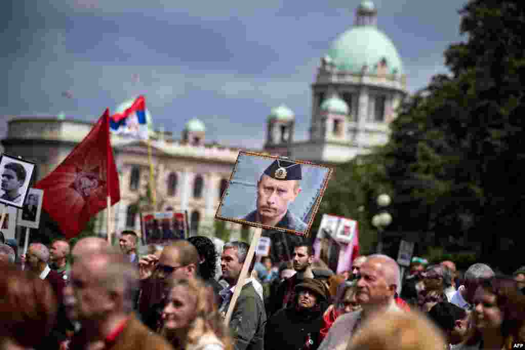 A man carries a portrait of Russian President Vladimir Putin during an Immortal Regiment march in central Belgrade, Serbia, on May 9. ( AFP/Andrej Isakovic)