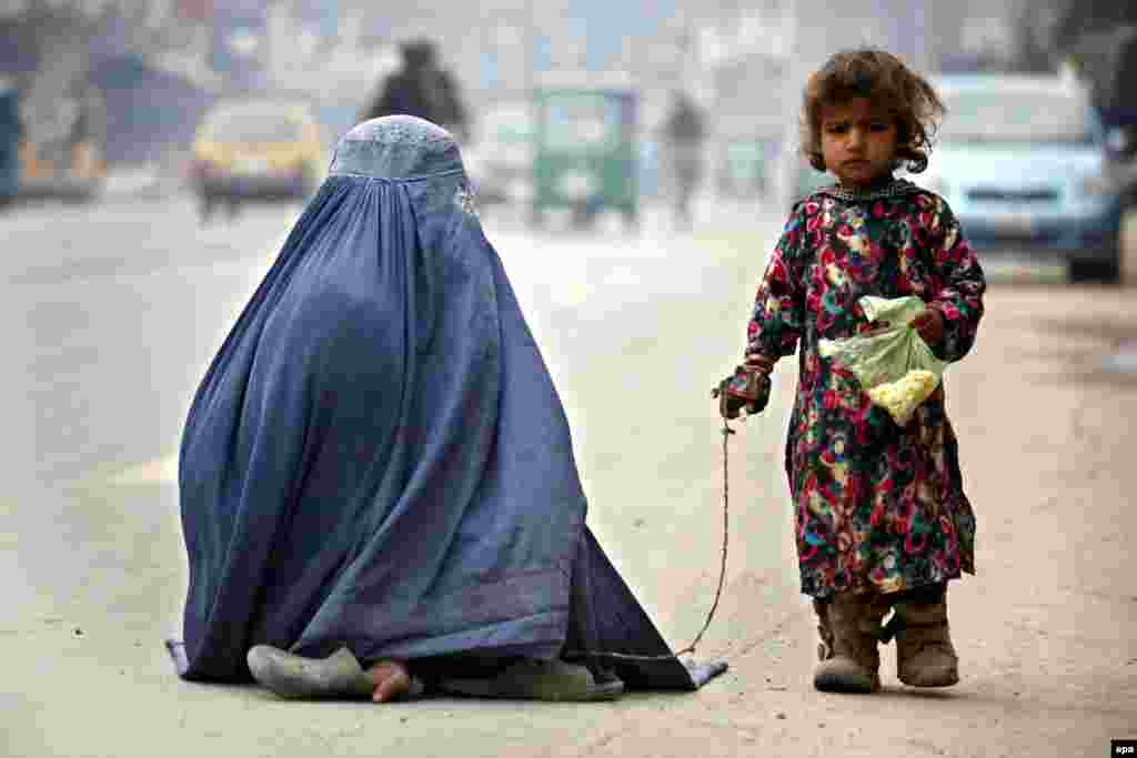 A burqa-clad mother and her daughter beg for alms on a road in Peshawar, Pakistan. (epa/Arshad Arbab)