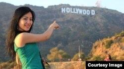 """Айгерим Сенгирбаева показывает на надпись: """"Голливуд"""" — в Лос-Анджелесе."""