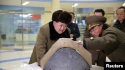 Жолбашчы Ким Чен Ын белгисиз жайда ракетанын дүрмөтүн көрүп жаткан учур.