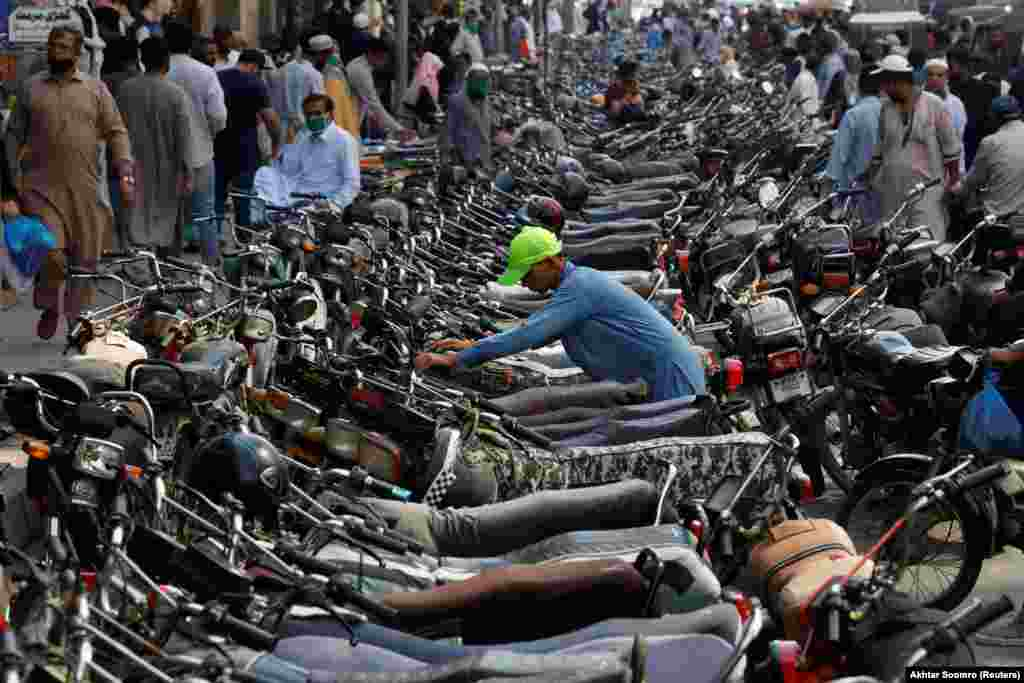 A Pakistani boy parks his motorcycle among hundreds of others outside a shopping bazaar after the easing of lockdown measures in Karachi on May 12. (Reuters/Akhtar Soomro)