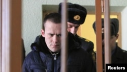 Former opposition campaigner Vasil Parfyankau is escorted by policemen into court in Minsk on February 17.
