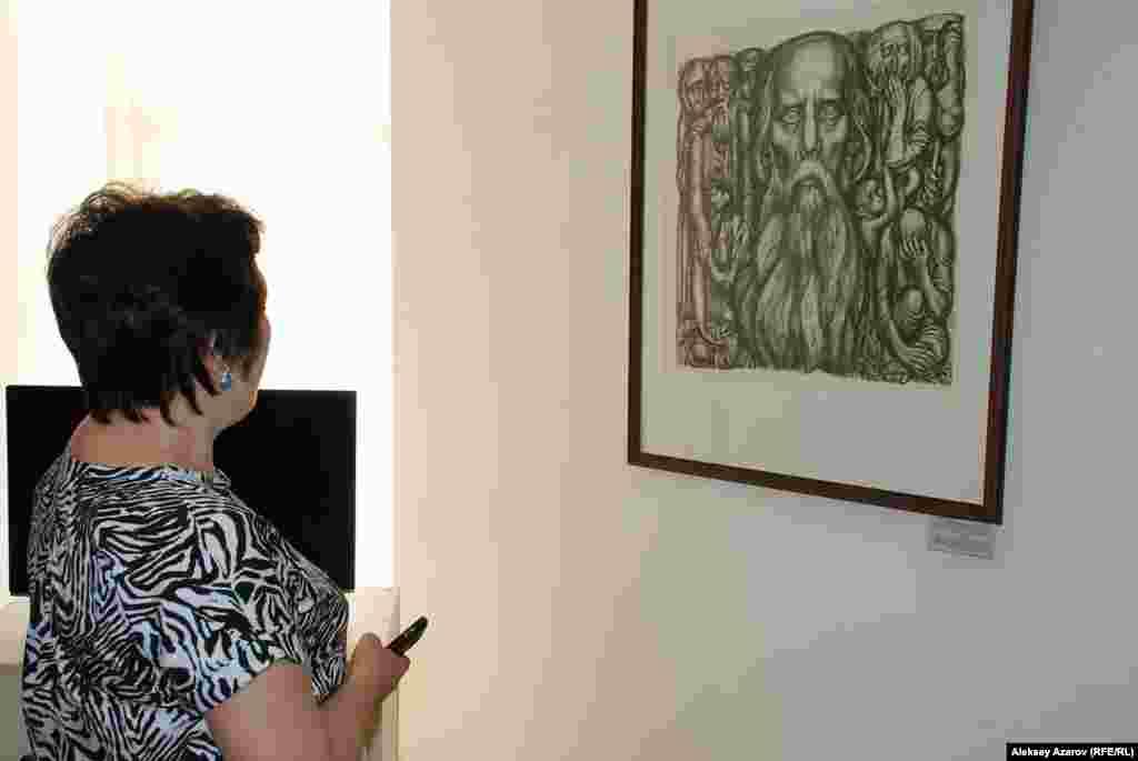 Посетительница рассматривает работу из серии иллюстраций к роману Михаила Салтыкова-Щедрина «История одного города». Сын художника, ВадимСидоркин, рассказал репортеру Азаттыка, что эта серия в 1975 годувышла отдельной книгой. Но весь тираж был арестован. Идеологиусмотрели в графике Сидоркина критику советского строя. Так, на одномиз листов были изображены советские дома, хотя в виду имелисьаракчеевские казармы эпохи российского императора Николая I.Стрельчиха Домашка на листе Евгения Сидоркина пьет советскую водку«Экстра».