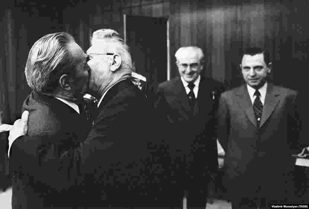 As Brezhnev locks lips with Nikolai Podgorny in the Kremlin in 1975, two elder statesmen (right) suffer instant demotion to third and fourth wheels.