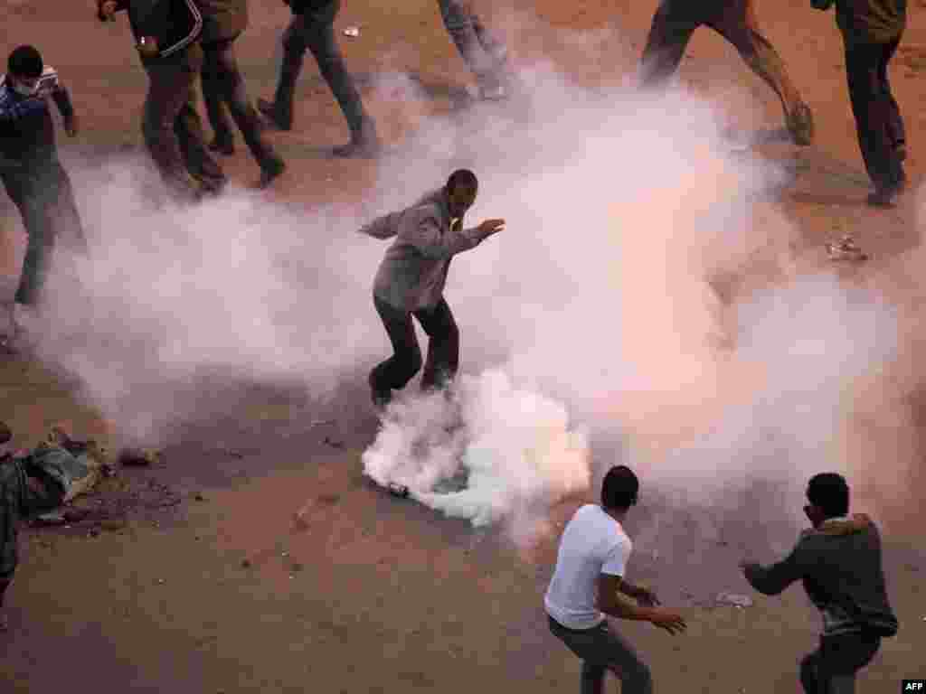 Anti-government demonstrators remove a tear gas canister thrown by police during clashes January 27.