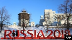 "A woman poses for pictures while standing behind giant letters reading ""Russia 2018"" in central Yekaterinburg on January 30 as Russia marks 500 days until the start of the FIFA World Cup 2018."