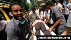 Раненого в давке на железнодорожной станции в Мумбаи несут на носилках в больницу. Мумбаи, 28 сентября 2017 года.