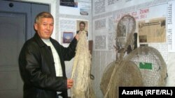 Хәмзә Камалов музейдагы балык тоту кирәк-яраклары янында