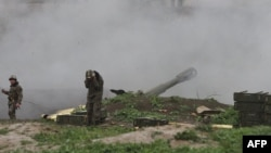 Nagorno-Karabakh -- Armenian servicemen of the self-defense army of Nagorno-Karabakh fire an artillery shell towards Azeri forces from their positions in the town of Martakert , April 3, 2016