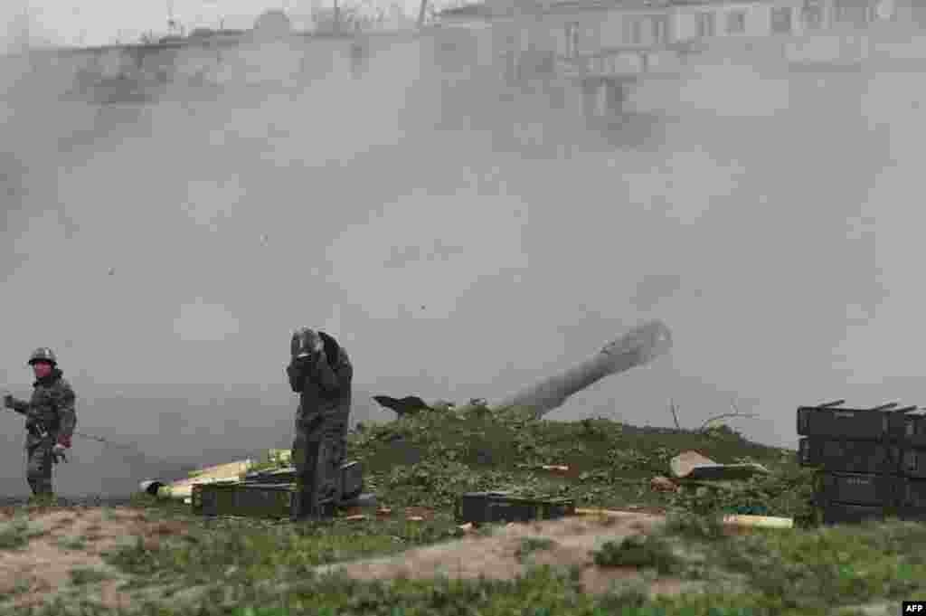 Armenian servicemen from the self-defense army of Nagorno-Karabakh fire an artillery shell toward Azerbaijani forces from their positions in the town of Martakert on April 3. (AFP/Vahram Baghdasaryan)