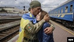 Український військовослужбовець обіймає свою дівчину після повернення з фронту. Київ, вересень 2015 року