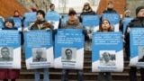 "Activists hold placards reading ""Free Sentsov"" as others hold pictures of 70 Ukrainian political prisoners jailed in Russia, including the sailors detained in the Azov Sea conflict, during a rally in front of the EU Embassy in Kyiv on December 11."