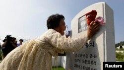 Женщина оплакивает погибшего на войне отца. Мемориальное кладбище в Пхеньяне, 25 июля 2013 года