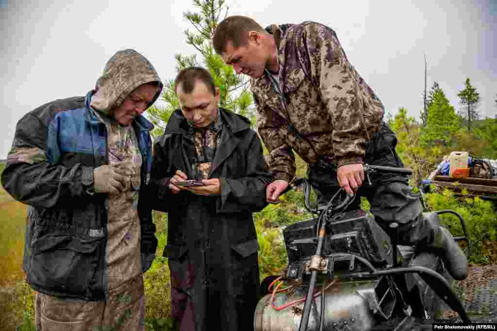 Sergey (left) and Vitaly Multanov (right) and Dmitry Laziamov use a GPS-enabled smartphone to find their way through the tundra.