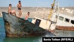 Мальчики прыгают в воду со старой лодки в поселке Баутино в Каспийском море. 3 мая 2013 года.