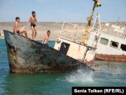 Дети на заброшенной лодке на берегу Каспийского моря. Поселок Баутино. 3 мая 2013 года. Иллюстративное фото.