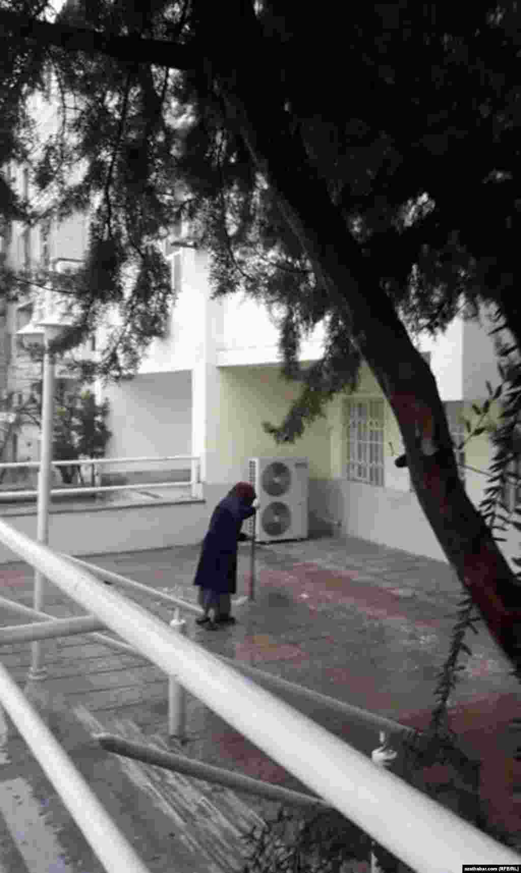 Işigini süpürýän aýal. Aşgabat, fewral, 2020.