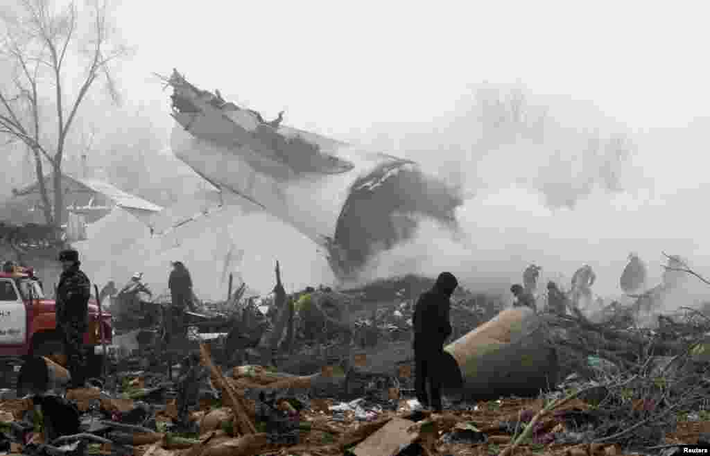 Rescue teams are seen at the crash site of a Turkish cargo jet near Manas airport outside Bishkek, Kyrgyzstan, on January 16. More than 30 people died in the incident. (Reuters/Vladimir Pirogov)
