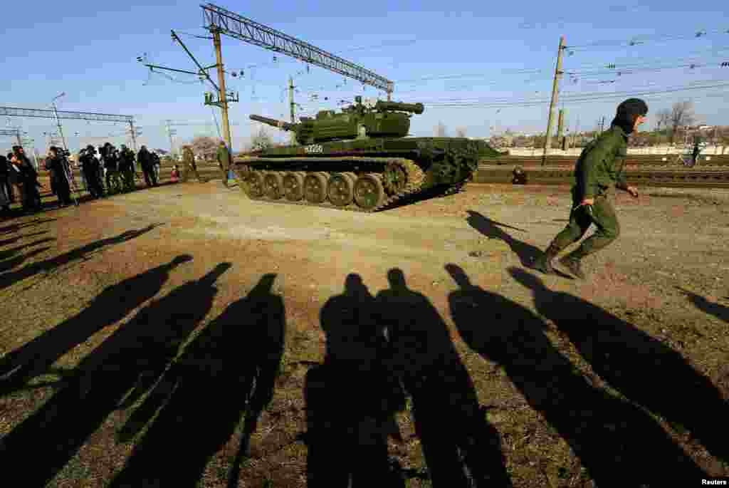 A Russian tank crew member runs in front of his T-72B tank after his arrival in Crimea in the settlement of Gvardeiskoye near the city of Simferopol. (Reuters/Yannis Behrakis)