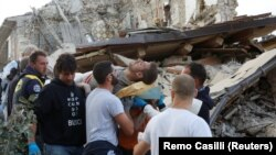 A man is carried away after been rescued alive from the ruins following an earthquake in Amatrice, central Italy, Aug 24, 2016