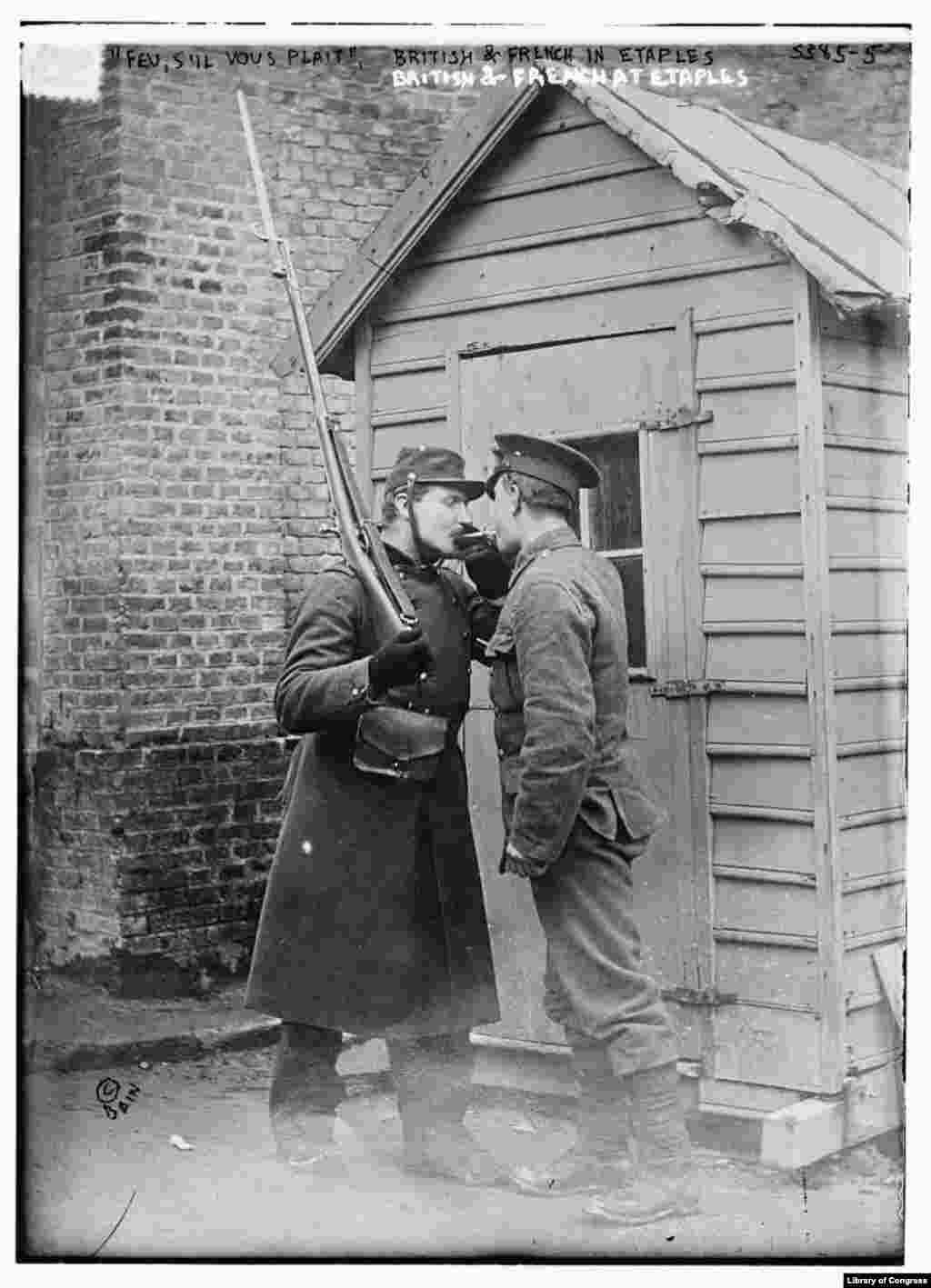 British and French soldiers light a cigarette at Etaples in northern France at the beginning of World War I. Although the source of the flu strain that devastated the world from 1918-1920 is disputed, many believe the pandemic began in this French military camp.