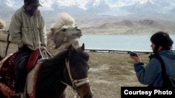 China -- RFE/RL Correspondent Janyl Jusupjan speaks with a trader at Kara-kol. Local Kyrgyz offer horses and camels for riding and sell small gifts to tourists. May 16, 2011.